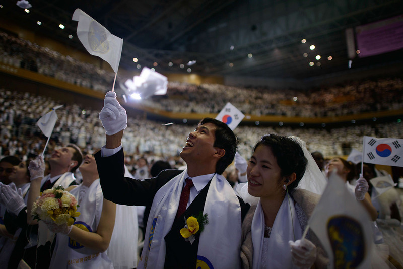 ". Couples wave flags during a mass wedding event held by the Unification Church in Gapyeong on February 12, 2014. Unification Church members forming 2500 couples from 52 countries were married in a mass wedding in South Korea -- only the second such event since the death of their ""messiah\"" and controversial church founder Sun Myung Moon. (ED JONES/AFP/Getty Images)"
