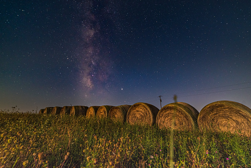 A row of round bales under the Milky Way