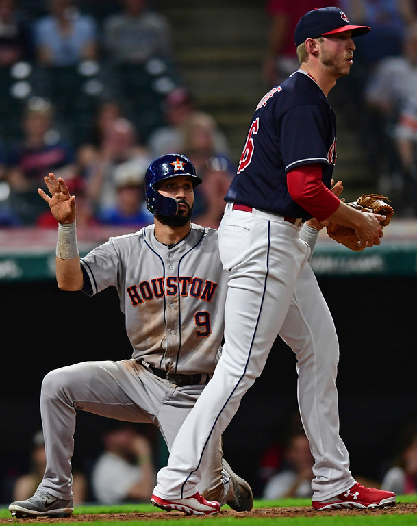 . Houston Astros\' Marwin Gonzalez celebrates after scoring a run on two-run single by Evan Gattis, while Cleveland Indians relief pitcher Oliver Drake walks past during the ninth inning of a baseball game Friday, May 25, 2018, in Cleveland. The Astros won 11-2. (AP Photo/David Dermer)
