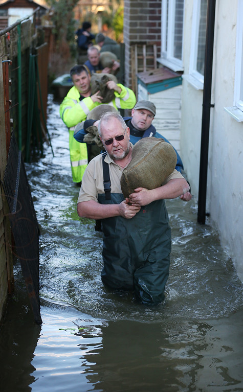 . Volunteers deliver sandbags to a property inundated with floodwater on February 11, 2014 in Wraysbury, England. The Environment Agency has issued severe flood warnings for a number of areas on the river Thames west of London.  (Photo by Peter Macdiarmid/Getty Images)