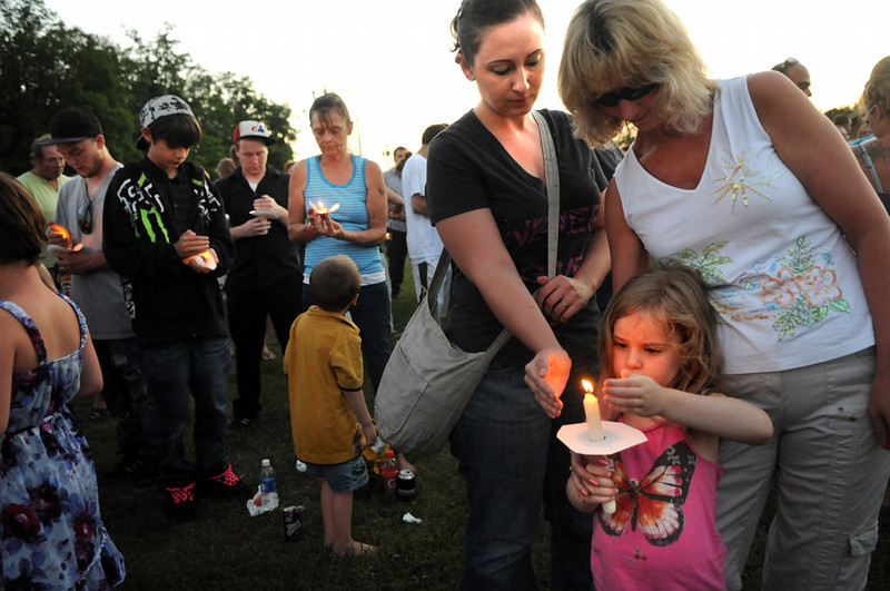 . Liliana Kolb of Little Canada, foreground, tries to keep her candle lit on a windy night with the help of her mom, Christina Kolb (black shirt) and her grandma Karen Murphy at a candlelight vigil for Isaiah Theis in Centuria on Thursday. Christina Kolb went to Sunrise Middle School in White Bear Lake with Shawn Theis, Isaiah\'s mom. (Pioneer Press: Jean Pieri)