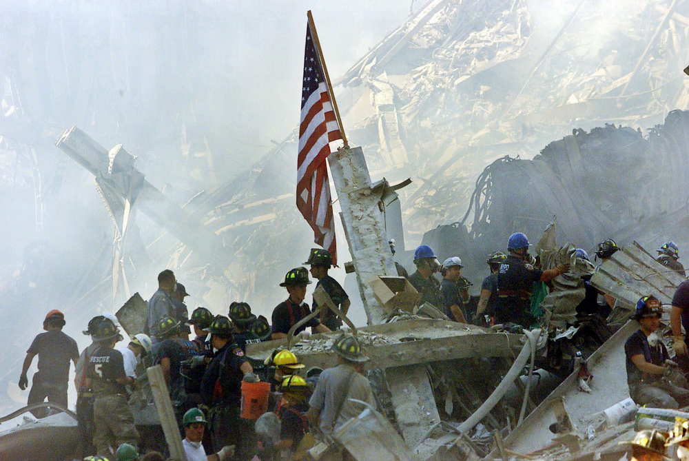 . An American flag flies over the rubble of the World Trade Center in New York, Sept. 13, 2001.    (AP Photo/Beth A. Keiser, file)