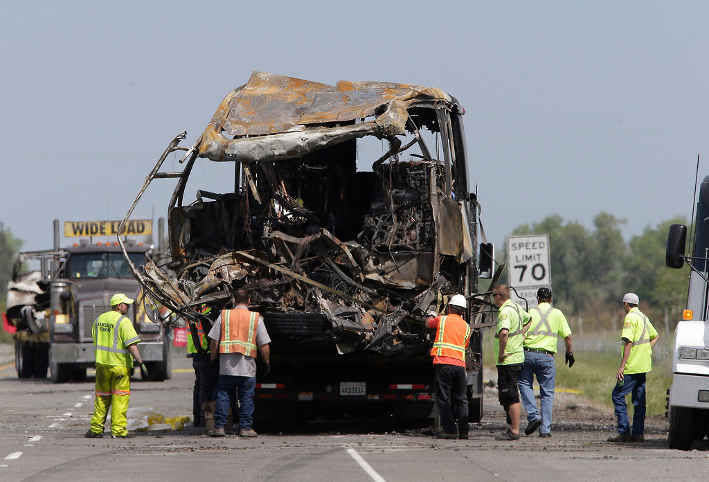 . The burned out remains of a tour bus involved in a fiery crash with FedEx truck, sits on a flatbed truck before being taken from the scene, Friday April 11, 2014 in Orland, Calif.  Ten people were killed and dozens injured in the fiery crash between the truck and the bus carrying high school students on a visit to a Northern California College, Thursday.(AP Photo/Rich Pedroncelli)