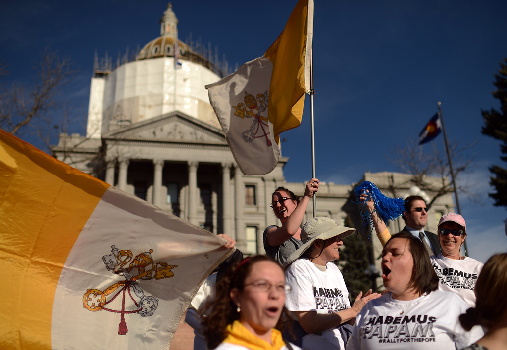 . DENVER, CO. - MARCH 13: Abby Kowitz of Denver with flag of Vatican City, top, and people celebrates election of the new pope with a march from Civic Center to the Cathedral Basilica of the Immaculate Conception. Jorge Bergoglio of Argentina was elected new pope. March 13, 2013. Denver, Colorado. (Photo By Hyoung Chang/The Denver Post)