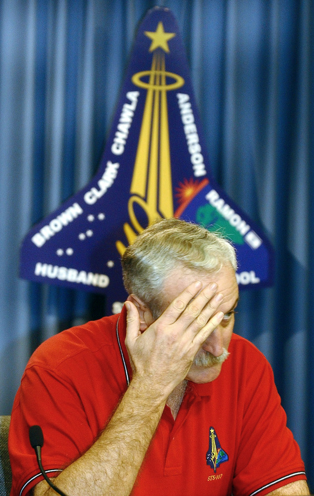 . NASA Administrator Sean O\'Keefe rubs his forehead prior to a news conference at Florida\'s Kennedy Space Center, Saturday, Feb. 1, 2003. NASA lost communication with the space shuttle Columbia Saturday after it broke apart in flames over Texas, killing all seven astronauts just minutes before they were to glide to a landing in Florida.(AP Photo/Orlando Sentinel, Red Huber)
