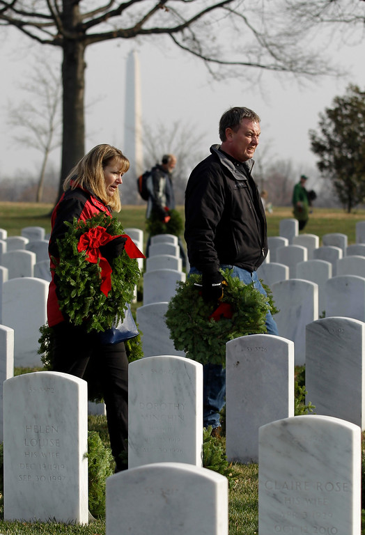 . A unidentified couple carry wreaths for placement at tombstones during Wreaths Across America\'s 150th anniversary, Saturday, Dec. 13, 2014, at Arlington National Cemetery in Arlington, Va. The Washington Monument is on the background. (AP Photo/Luis M. Alvarez)
