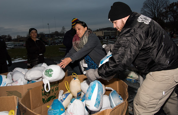 11/19/18 Wesley Bunnell | Staff HRA distributed Thanksgiving meals at their Osgood Ave location on Monday afternoon. Liduvina Salgado & Dalvin Ramirez load frozen turkeys into bins for distribution.
