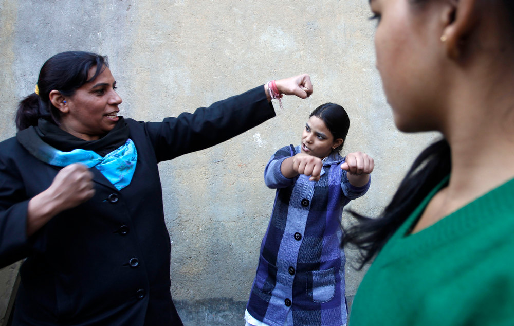 Description of . An Indian woman, left, teaches young girls martial arts at a self defense program in New Delhi, India, Thursday, Dec. 20, 2012. The hours-long gang-rape and near-fatal beating of a 23-year-old student on a bus in New Delhi triggered outrage and anger across the country as Indians demanded action from authorities who have long ignored persistent violence and harassment against women. (AP Photo/Tsering Topgyal)