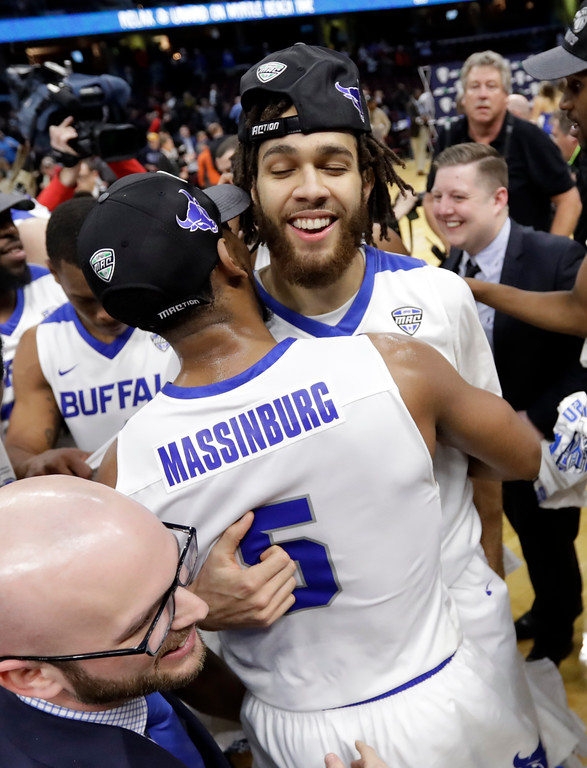 . Buffalo\'s Jeremy Harris, right, hugs CJ Massinburg after Buffalo defeated Toledo 76-66 during an NCAA college basketball championship game of the Mid-American Conference tournament, Saturday, March 10, 2018, in Cleveland. (AP Photo/Tony Dejak)