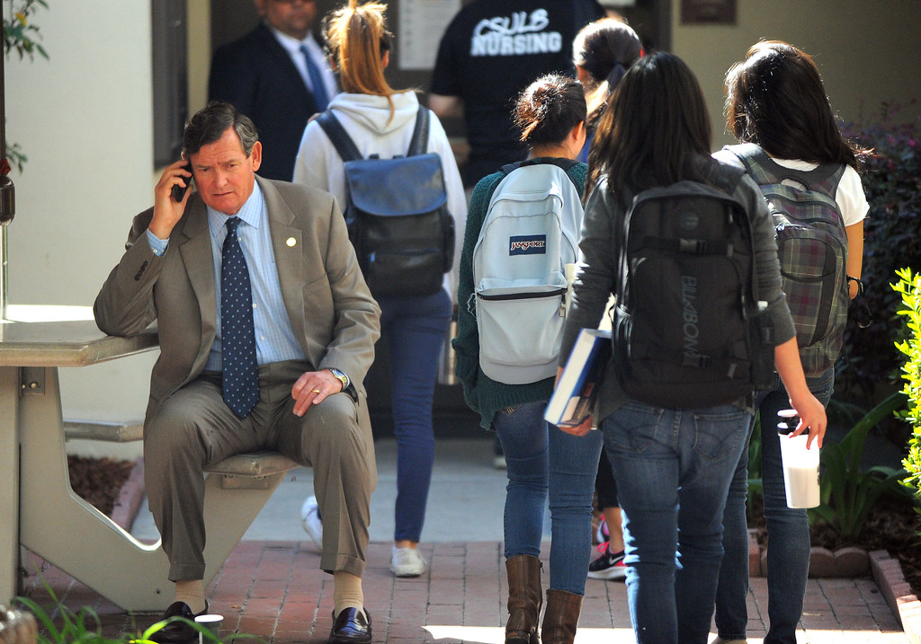 . CSU Chancellor Timothy P. White takes a phone call as nursing students head to class during his tour of Cal State Long Beach on Monday, October 14, 2013.  (Photo by Scott Varley, Daily Breeze)