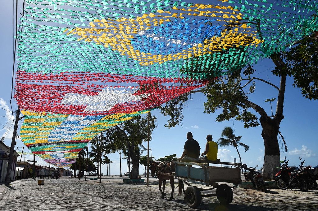 . A horse-drawn carriage travels along a street under a canopy of national flags of countries participating in the forthcoming 2014 FIFA World Cup in Porto Seguro on June 10, 2014, ahead of the start of the tournament in Brazil. AFP PHOTO / ANNE-CHRISTINE POUJOULAT/AFP/Getty Images