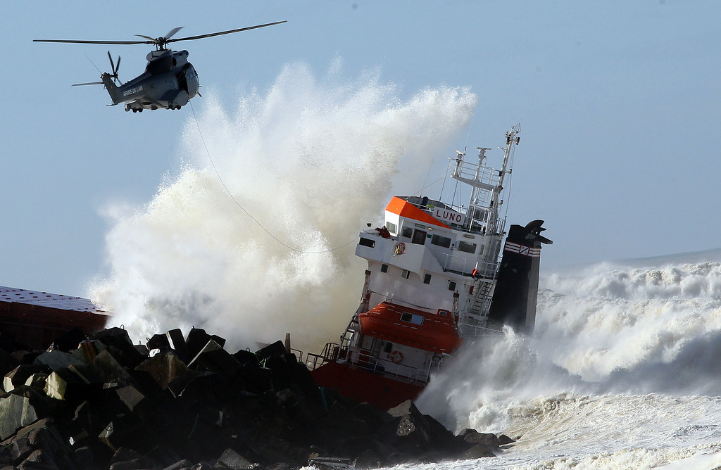 """. A military helicopter flies over a Spanish cargo ship \""""Luno\"""" that slammed into a jetty in choppy Atlantic Ocean waters and broke in two, off Anglet, southwestern France, Wednesday, Feb. 5, 2014. . (AP Photo/Bob Edme)"""