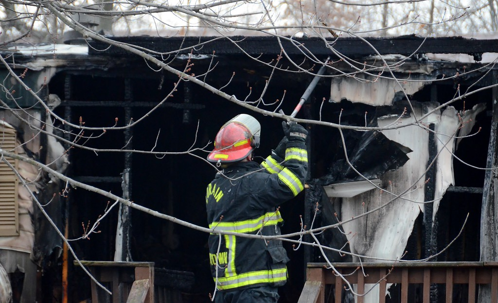 . A Lorain firefighter searches for hot spots within a trailer in the 3900 block of Reid Avenue on Dec. 23 after an early morning fire killed a 9-year-old girl and injured one other person.  (Kelsey Leyva � The Morning Journal)