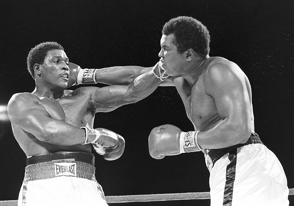 Description of . Trevor Berbick, left, and Muhammad Ali seem to have an equal reach as they slug it out during a Friday night boxing match in this  Dec. 12, 1981 file photo in Nassau, Bahamas.   Berbick, who lost his heavyweight title to Mike Tyson and was the last boxer to fight Muhammad Ali, was found dead Saturday, Oct. 28, 2006, in a church courtyard in Kingston, Jamaica, police said. He was 52. (AP Photo)