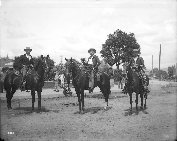 Governor Figueroa and aids dressed up as Spanish caballeros, riding on horses near the Plaza Church during La Fiesta de Los Angeles, ca.1901
