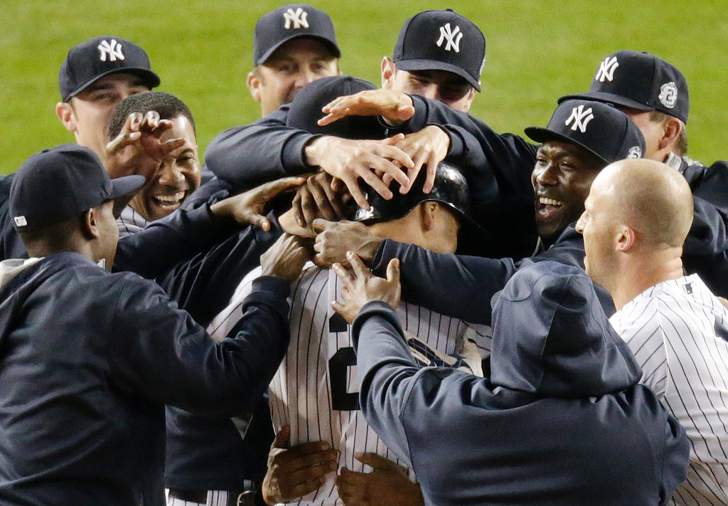 . New York Yankees\' Derek Jeter (2) celebrates with teammates after driving in the winning run against the Baltimore Orioles in the ninth inning of a baseball game, Thursday, Sept. 25, 2014, in New York. The Yankees won 6-5 in Jeter\'s final home game. (AP Photo/Bill Kostroun)