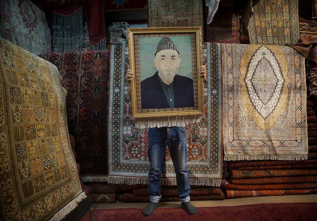 . In this Sunday, March 30, 2014 file photo, an Afghan carpet seller holds up a framed carpet depicting Afghan President Hamid Karzai in his store in Kabul, Afghanistan. (AP Photo/Anja Niedringhaus, File)