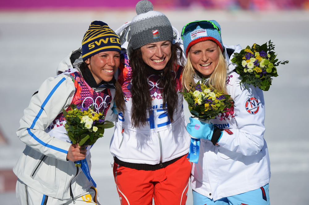 . (L-R) Silver medalist Charlotte Kalla of Sweden, gold medalist Justyna Kowalczyk of Poland and bronze medalist Therese Johaug of Norway celebrate on the podium during the flower ceremony for the Women\'s 10 km Classic during day six of the Sochi 2014 Winter Olympics at Laura Cross-country Ski & Biathlon Center on February 13, 2014 in Sochi, Russia.  (Photo by Harry How/Getty Images)