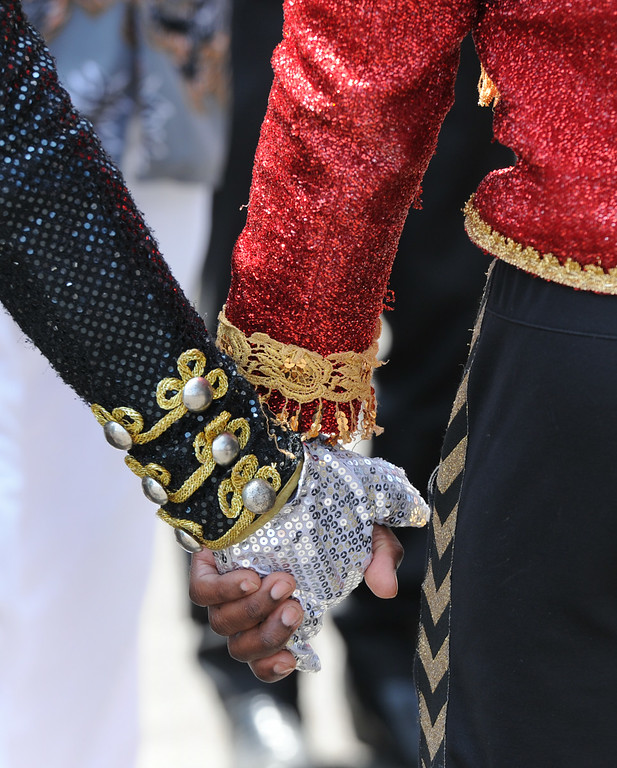 . Jackson fans hold hands during a moment of silence. Michael Jackson impersonators, and fans gathered at the Great Mausoleum at Forest Lawn Memorial Park in Glendale to honor Jackson on the 5th anniversary of his death.  Glendale, CA. 6/25/2014 (Photo by John McCoy Daily News)