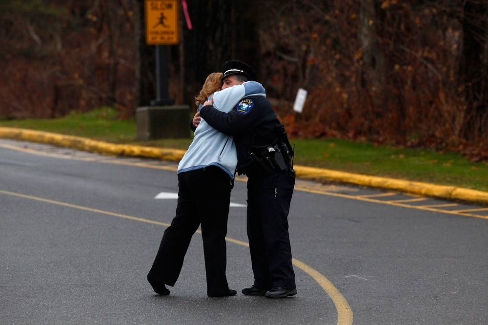 Description of . Easton police officer J. Sollazzo hugs a woman at school in Newtown, Connecticut December 18, 2012. The schools of Newtown, which stood empty in the wake of a shooting rampage that took 26 of their own, will again ring with the sounds of students and teachers on Tuesday as the bucolic Connecticut town struggles to return to normal. REUTERS/Eric Thayer