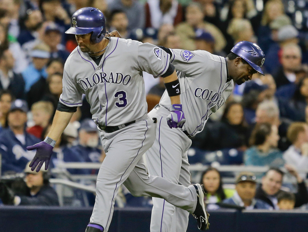 . Colorado Rockies\' Michael Cuddyer gets a low-five from third base coach Stu Cole after blasting a two-run homer against the San Diego Padres in the fourth inning of a baseball game, Saturday April 13, 2013, in San Diego. (AP photo/Lenny Ignelzi)
