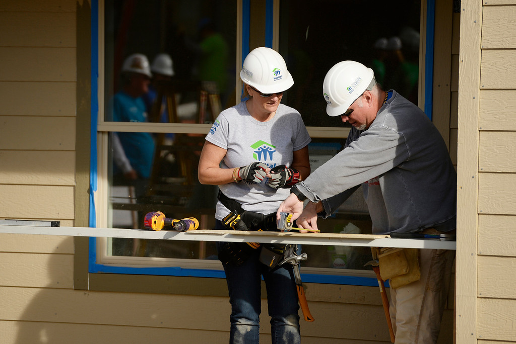 . DENVER, CO - OCTOBER 09: Trisha Yearwood and Garth Brooks work on building a home during Habitat for Humanity\'s Carter Work Project event in the Globeville Neighborhood in Denver, October 09, 2013. The Humanity\'s Carter Work Project will complete 11 new townhouses. (Photo By RJ Sangosti/The Denver Post)