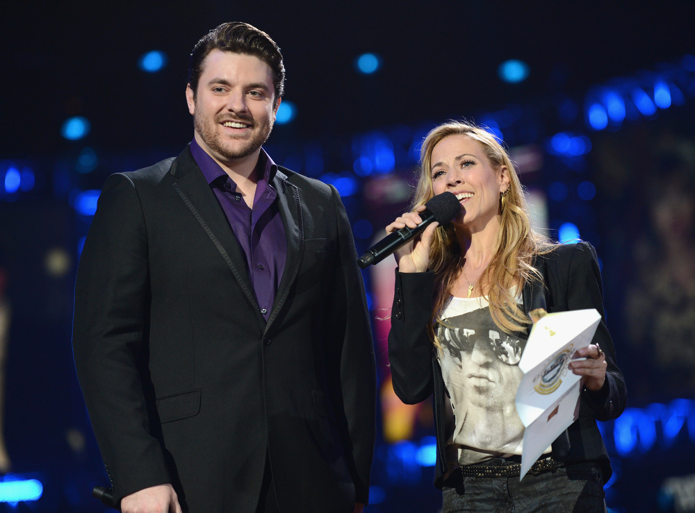 Description of . Chris Young and Sheryl Crow speak onstage at The GRAMMY Nominations Concert Live!! held at Bridgestone Arena on December 5, 2012 in Nashville, Tennessee.  (Photo by Michael Kovac/Getty Images)