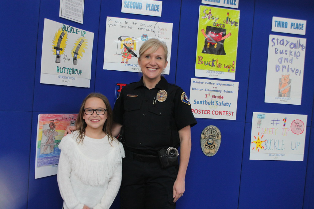 . Kristi Garabrandt � The News-Herald <br> Mentor police officer, Colleen Petro stands with Grace Horton, one of the winners of the Mentor Police Department third grade seatbelt safety poster contest, during the 36th Annual Heroes Day held at Great Lakes Mall, May 12.