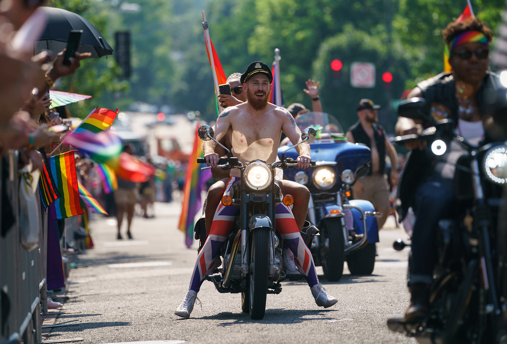 . Scott Simpson and his husband, Michael Clarke, ride with the Out Riders Women\'s Motorcycle Club, as Prince Harry and Meghan Markle in the Capital Pride Parade in Washington, Saturday, June 9, 2018. The yearly event is hosted by and in support of the LGBTQ+ community and moves through the Dupont Circle and Logan Circle neighborhoods of Washington. (AP Photo/Carolyn Kaster)