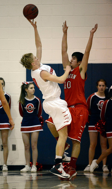 . Chaparral\'s Jake Holtzmann (10) takes an awkward shot over Brighton\'s Jaren Snyder during the fourth quarter February 27, 2013. Chaparral defeated Brighton 59-47. (Photo By John Leyba/The Denver Post)