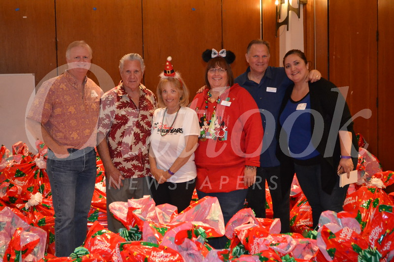 John Cervenka, Jules Marcogliese, Mary Kay Hunefeld, Ginger Mort, Vance Weisbruch and Lupe Barraza helped give presents to families.