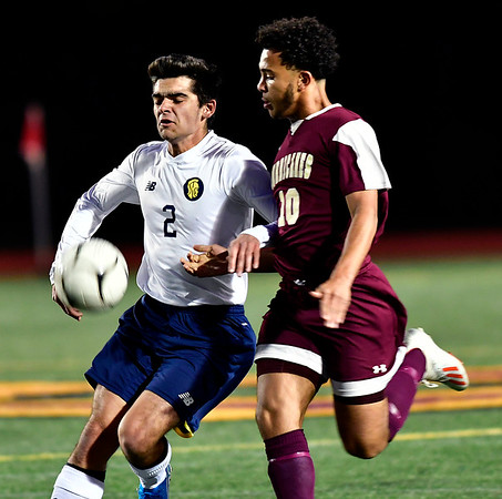 10/24/2019 Mike Orazzi | StaffrNew Britain's Abdul Jallaha (10) and Simsbury's Nicholas Savino (2) during Thursday night's boys soccer at Veterans Stadium in New Britain.