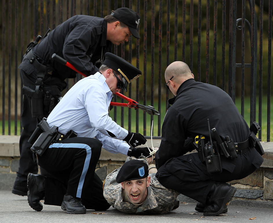 """. WASHINGTON - NOVEMBER 15:  Members of the U.S. Park Police arrest a veteran and gay rights activist who has handcuffed himself to the fence of the White House during a protest November 15, 2010 in Washington, DC. Activists staged the protest to call on the Obama Administration and Senate Majority Leader Harry Reid to keep their promises on repealing the \""""Don?t Ask, Don?t Tell\"""" policy, which prevented gay people from serving openly, during the lame-duck session of the Congress.  (Photo by Alex Wong/Getty Images)"""