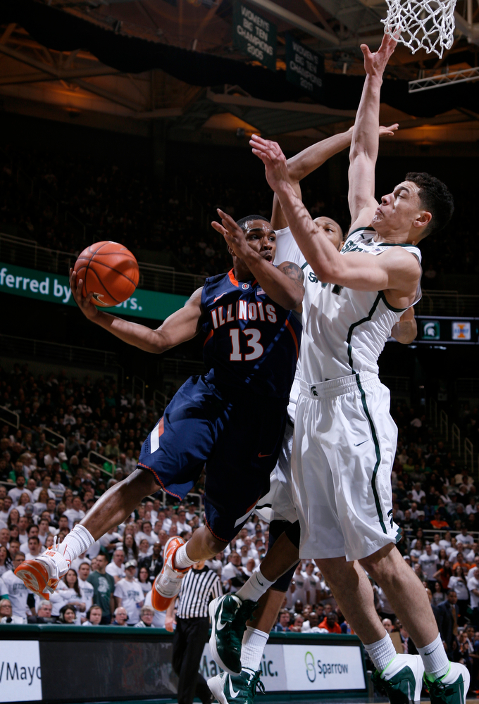 . Illinois\' Tracy Abrams (13) dishes off against Michigan State\'s Gavin Schilling, right, and Adreian Payne during the first half of an NCAA college basketball game, Saturday, March 1, 2014, in East Lansing, Mich. (AP Photo/Al Goldis)
