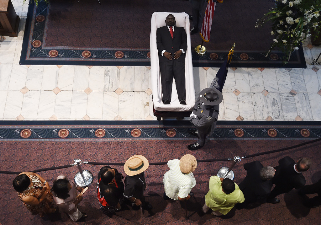 . A South Carolina Highway Patrol honor guard member stands over Sen. Clementa Pinckneyís body during a public viewing in the Statehouse, Wednesday, June 24, 2015, in Columbia, S.C. President Barack Obama is scheduled to deliver the eulogy at Pinckney\'s funeral Friday morning at the College of Charleston. Pinckney was one of those killed in a mass shooting at the Emanuel AME Church in Charleston. (AP Photo/Rainier Ehrhardt)