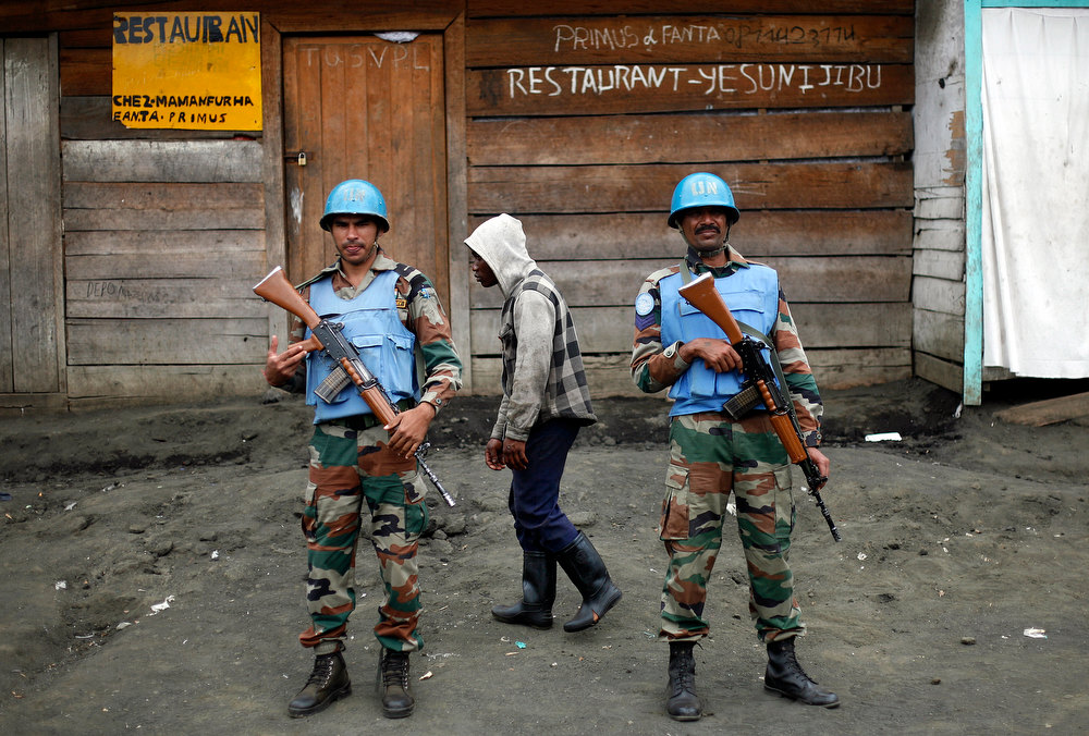 . Two MONUSCO UN soldiers stand guard in Goma\'s port as Police Nationale du Congo officers who fled Goma when M23 rebels took over the city Nov. 18 2012, return on a barge to the port of Goma, eastern Congo, Friday Nov. 30, 2012. The police force were returning to resume control on Friday, as had been agreed by the regional bloc. Rebels in Congo believed to be backed by Rwanda postponed their departure Friday from the key eastern city of Goma by 48 hours for ìlogistical reasons,î defying for a second time an ultimatum set by neighboring African countries and backed by Western diplomats. The delay raises the possibility that the M23 rebels donít intend to leave the city they seized last week, giving credence to a United Nations Group of Experts report which argues that neighboring Rwanda is using the rebels as a proxy to annex territory in mineral-rich eastern Congo. (AP Photo/Jerome Delay)