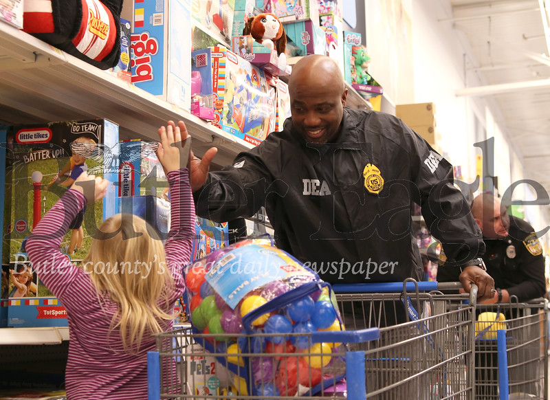 DEA special agent Paris Pratt high fives his Shop with a Cop child, Myla, at the Butler Area School District and Butler Walmart event  Friday. Seb Foltz/Butler Eagle