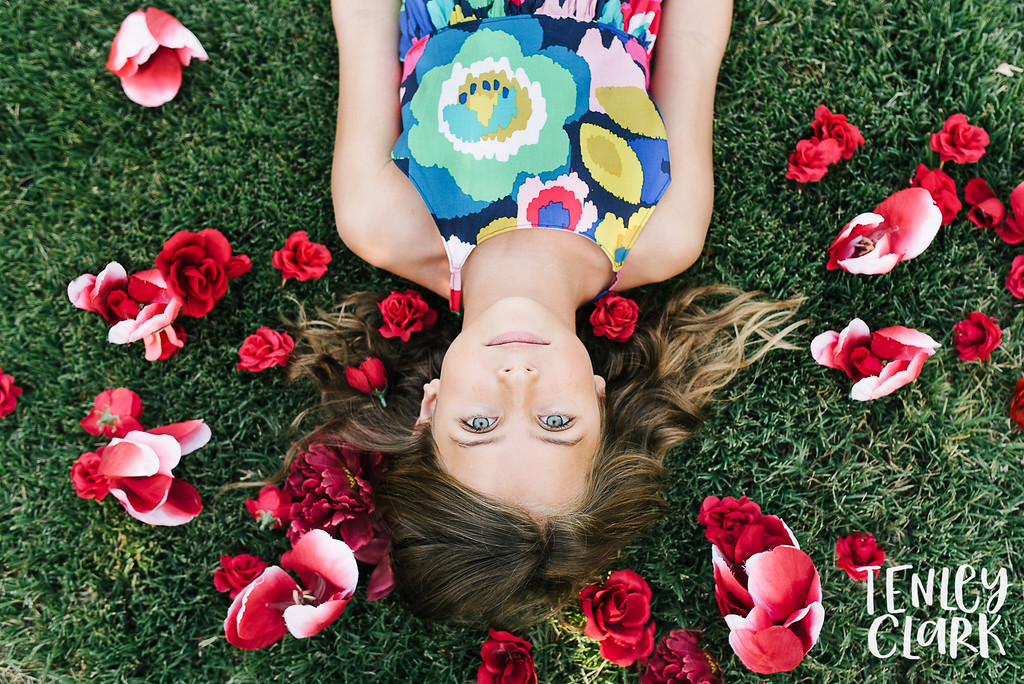 Playful kids fashion editorial-style commercial brand shoot with two girls playing in a garden for Gold Magnolia kids clothing boutique by Tenley Clark Photography. Models: Sofia and Olivia. Girl laying in grass with red flowers