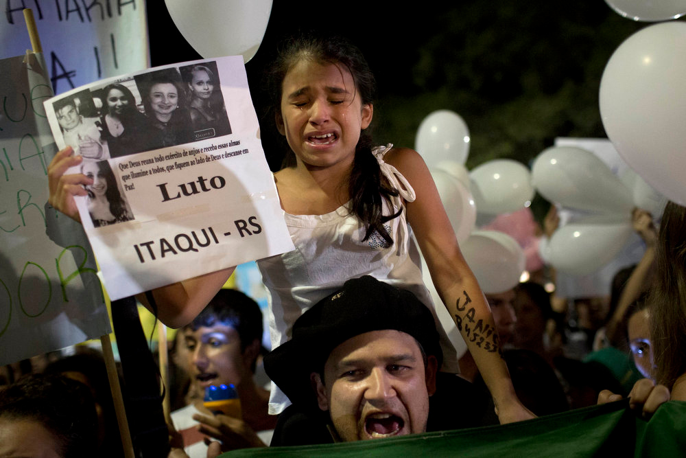 Description of . A girl cries during a march in a plaza near the Kiss nightclub honoring the victims of early Sunday's fatal fire inside the club in Santa Maria, Brazil, Monday, Jan. 28, 2013. All the elements were in place for the tragedy at the Kiss nightclub early Sunday. The result was the world's worst fire of its kind in more than a decade, with 231 people dead and this southern Brazilian college town in shock and mourning.(AP Photo/Felipe Dana)