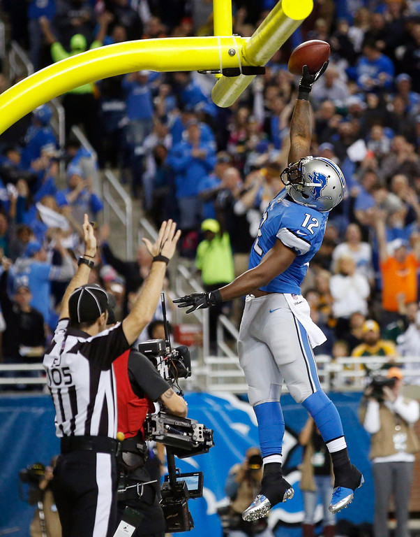 . Detroit Lions wide receiver Jeremy Ross (12) dunks the ball after scoring on a 5-yard pass reception during the second quarter of an NFL football game against the Green Bay Packers at Ford Field in Detroit, Thursday, Nov. 28, 2013. (AP Photo/Rick Osentoski)
