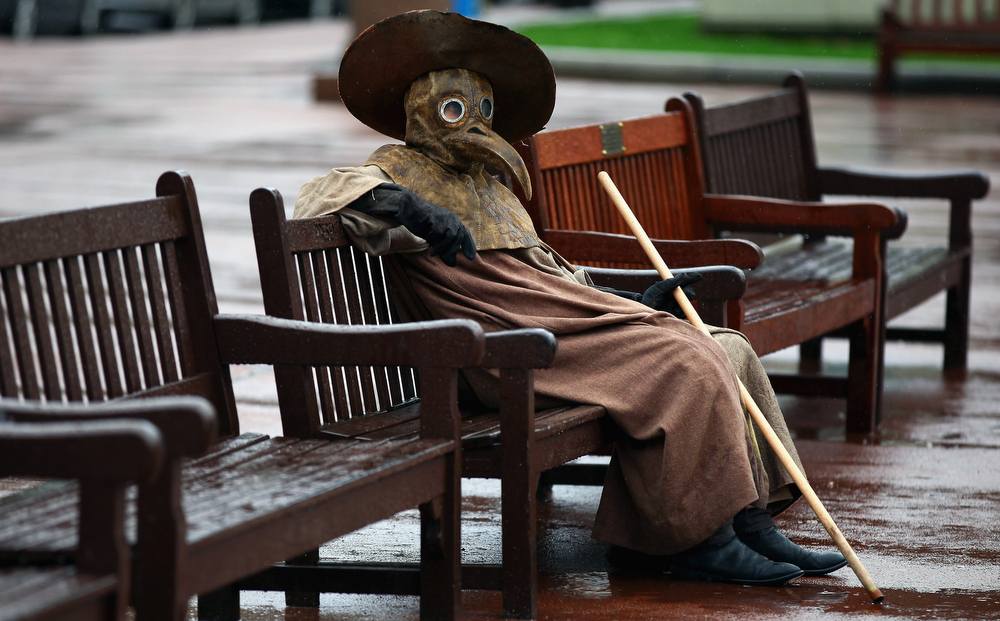 ". Frank To, Glasgow based artist dressed in a medieval Plague Doctor costume, sits on a bench in George Square on March 31, 2011 in Glasgow, Scotland. The artist was promoting his first major exhibition in two years, ""The Human Condition\"", which opens tomorrow at the Leith Gallery in Edinburgh. The artist is showing a series of pictures which depict Mediaeval Plague Doctors, which have fascinated the artist for the last three years.  (Photo by Jeff J Mitchell/Getty Images)"