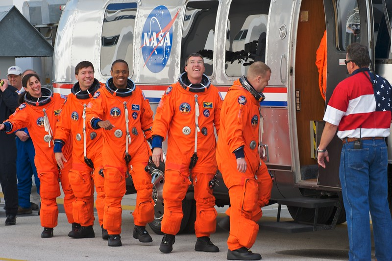 02/24/2011 -- Cape Canaveral, Florida -- Wearing their orange launch-and-entry suits, space shuttle Discovery's STS-133 crew board the Astrovan at the Operations and Checkout Building at Kennedy Space Center. The van will transport them to Launch Pad 39A. From left to right are Mission Specialists Nicole Stott, Michael Barratt, Steve Bowen, and Alvin Drew, and Pilot Eric Boe.