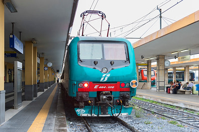 E464-106 waits at Catania Platform 1 with a wet northbound train