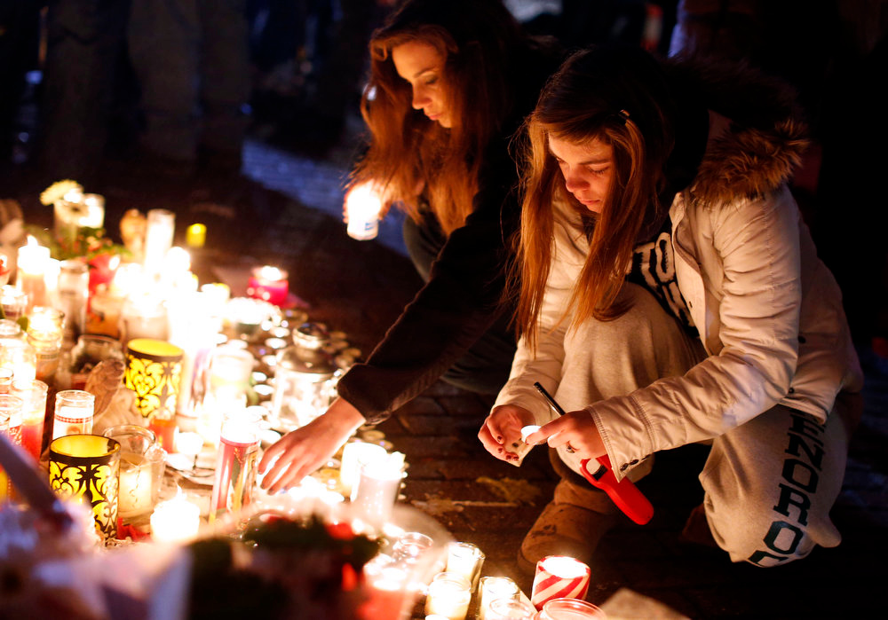 . Visitors light candles at a memorial to shooting victims, Monday, Dec. 17, 2012, in Newtown, Conn. A gunman walked into Sandy Hook Elementary School in Newtown Friday and opened fire, killing 26 people, including 20 children. (AP Photo/Jason DeCrow)