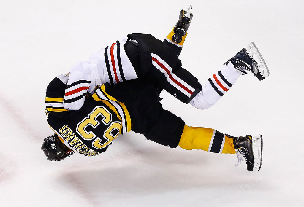 . Brad Marchand #63 of the Boston Bruins and Andrew Shaw #65 of the Chicago Blackhawks go airborne while fighting toward the end of the third period in Game Three of the Stanley Cup Final on June 17, 2013 at TD Garden in Boston, Massachusetts. (Photo by Jared Wickerham/Getty Images)