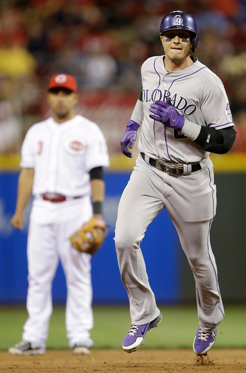 . Colorado Rockies\' Troy Tulowitzki rounds the bases past Cincinnati Reds second baseman Cesar Izturis (3) after Tulowitzki hit a two-run home run off relief pitcher Sam LeCure in the eighth inning of a baseball game, Tuesday, June 4, 2013, in Cincinnati. Colorado won 5-4. (AP Photo/Al Behrman)