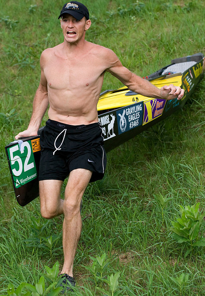 7/24/10 -ALL - The 63rd annual AuSable River Canoe Marathon took place in Grayling, Michigan on July 24 and 25th, 2010.  A record 94 teams began with a Lemans-style running start, portaging 6 dams and paddling 120 miles to the finish in Oscoda Sunday.    Nick Walton of Grayling drags his 18.5-foot carbon fiber canoe down Cooke Dam.  Nick and his partner Josh Sheldon finished 3rd with a time of 14 hours 39 minutes.  (Photo by Mark Bialek)