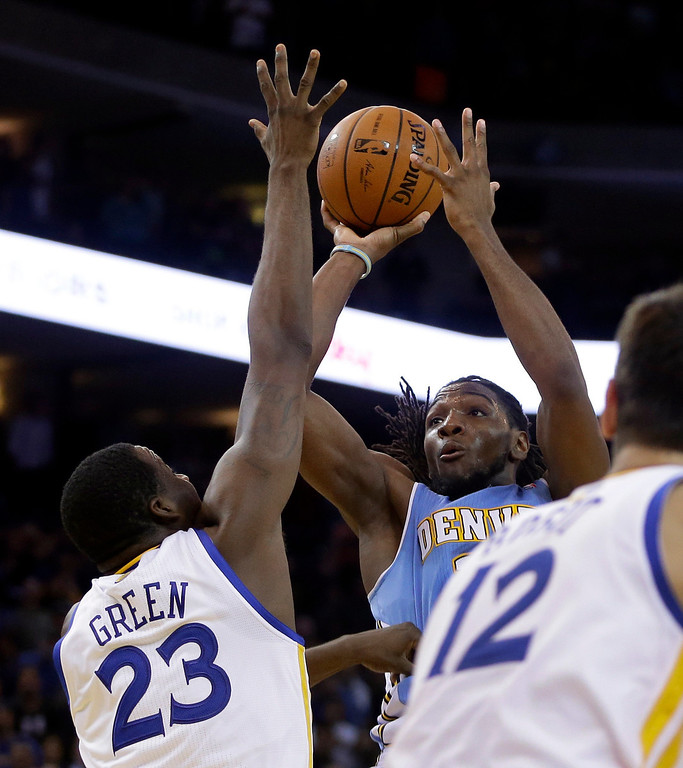 . Denver Nuggets\' Kenneth Faried shoots over Golden State Warriors\' Draymond Green (23) during the second half of an NBA basketball game Thursday, April 10, 2014, in Oakland, Calif. The basket game Denver a 100-99 win. (AP Photo/Ben Margot)