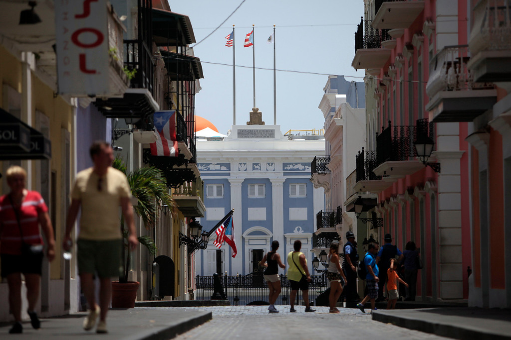 . People walk on the street in front of the governor�s mansion on the background in Old San Juan, Puerto Rico, Monday, June 29, 2015. International economists released a critical report on Puerto Rico\'s economy Monday on the heels of the governor\'s warning that the island can\'t pay its $72 billion public debt.(AP Photo/Ricardo Arduengo)