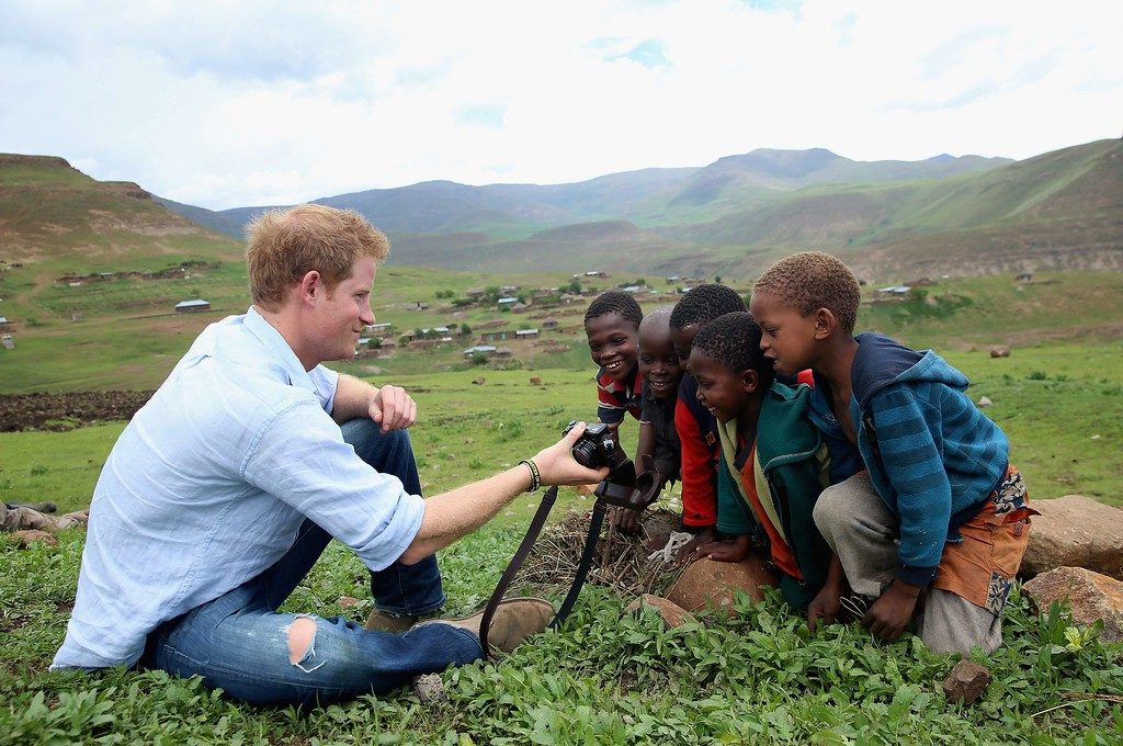 . Britain\'s Prince Harry shows children a photograph he has taken on a camera during a visit to a herd boy night school constructed by Sentebale in Mokhotlong, Lesotho, on December 8, 2014. Chris Jackson/AFP/Getty Images